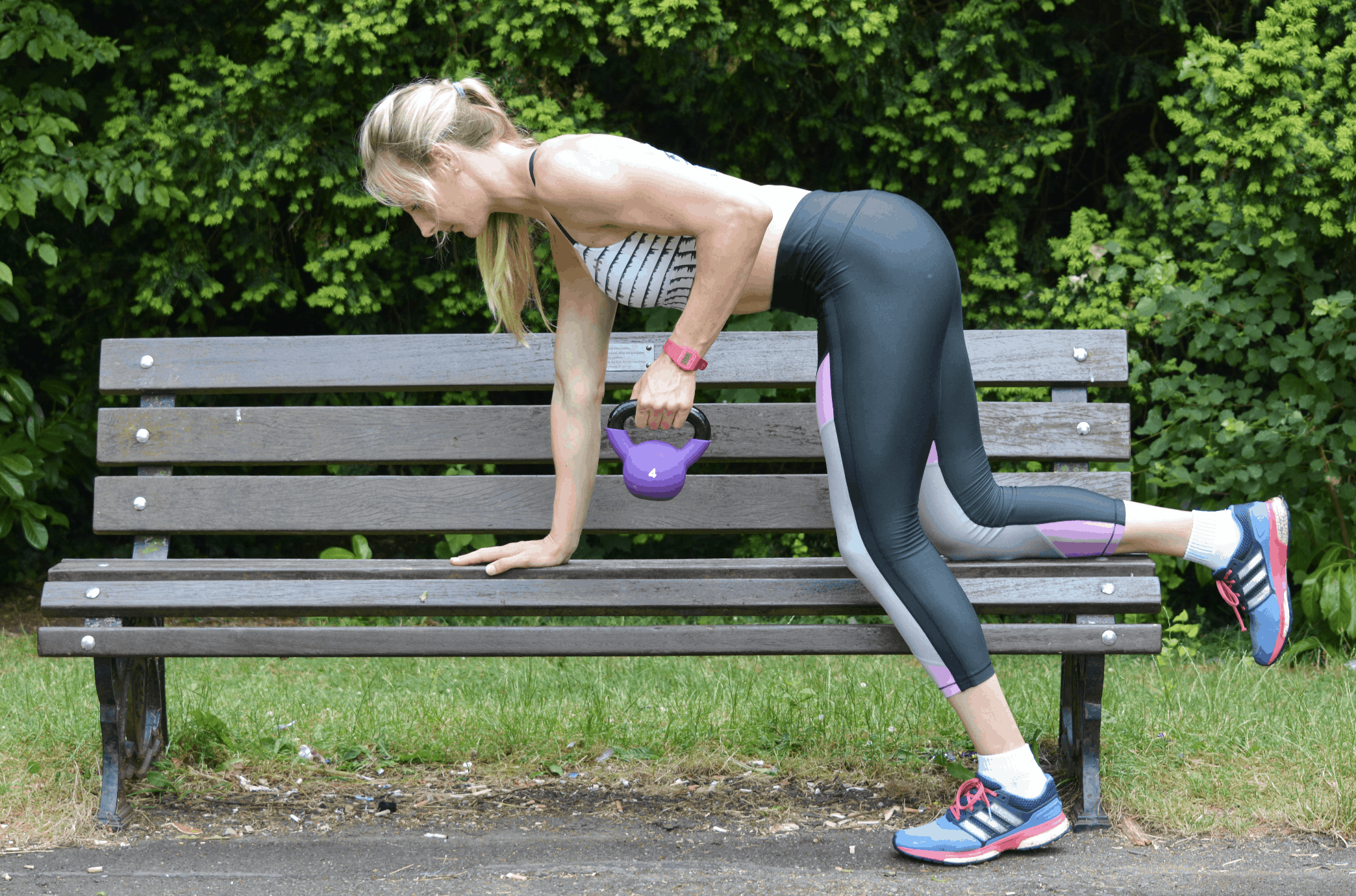 a girl is using a park bench to perform a single-arm kettlebell row.